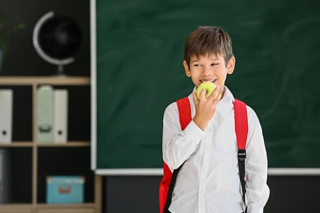 Aluno comendo maçã contra turva na escola