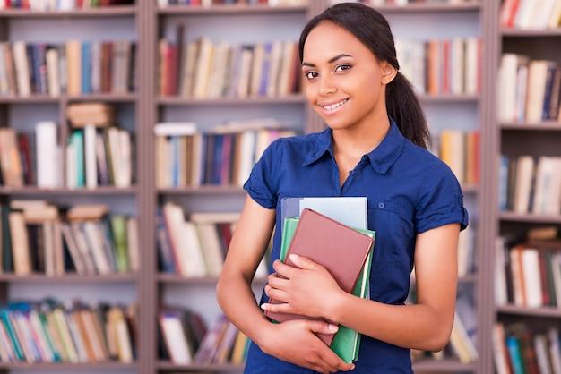 Aluno confiante. linda aluna africana segurando livros e sorrindo enquanto está na biblioteca