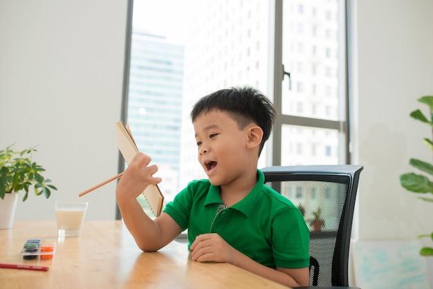 Aluno da ásia estudando e fazendo a lição de casa em casa, na mesa, educação em casa, pensando em ação