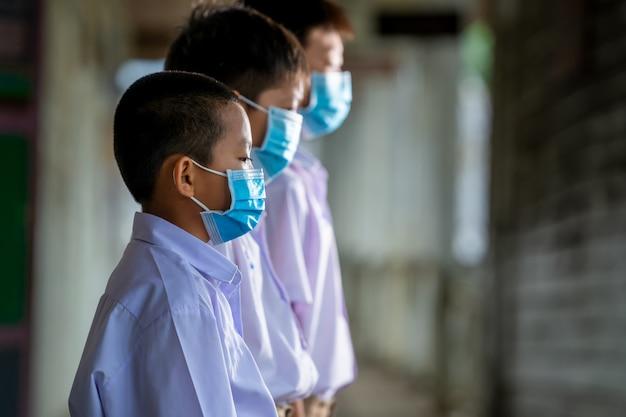 Aluno da ásia usa máscaras de proteção para segurança na escola primária.