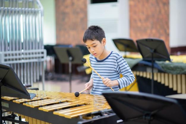 Aluno da escola de artes tocando instrumento de percussão