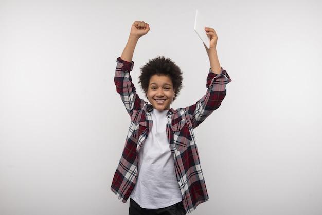 Aluno da escola. garoto inteligente e legal levantando as mãos enquanto fica feliz por ter vencido o concurso da escola