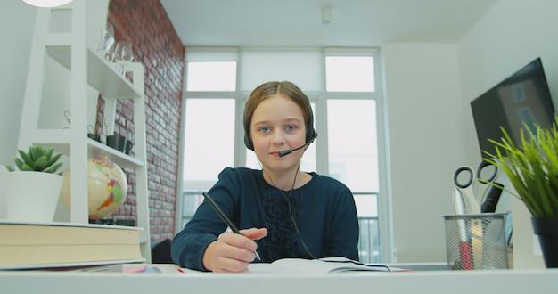 Aluno da escola linda garota usando fones de ouvido, aprendizagem à distância online