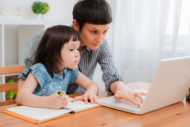 Aluno da escola mãe e filho em casa em um laptop, aprendendo a lição de casa. educação em casa eletrônica durante o período de pandemia e coronavírus. treinamento de assistência aos pais.