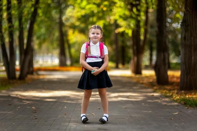 Aluno da escola primária. menina com mochila ao ar livre. início das aulas. primeiro dia de outono.