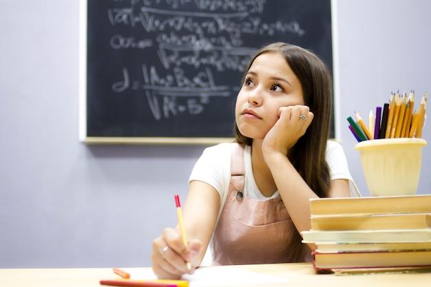 Aluno da escola senta-se em uma mesa em uma lição