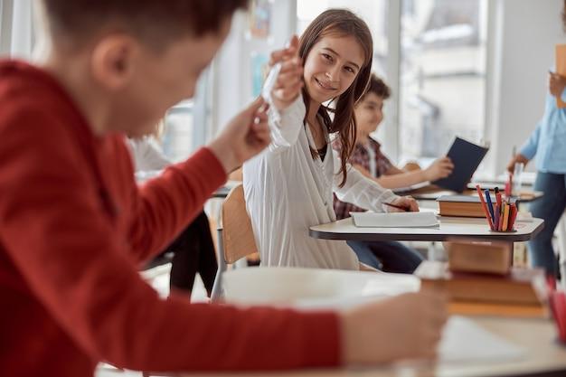 Aluno dá lápis para seu colega enquanto está sentado na mesa enquanto o professor fala na sala de aula.