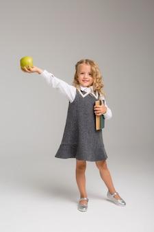 Aluno da primeira série com livros e uma maçã sorrindo sobre um fundo brilhante