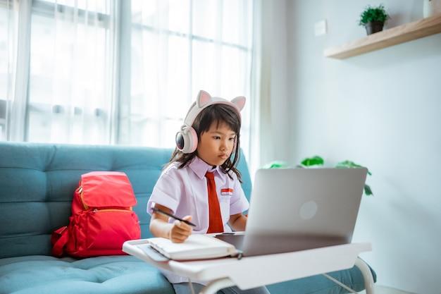 Aluno da primeira série com uniforme durante o estudo da aula online com o professor em casa