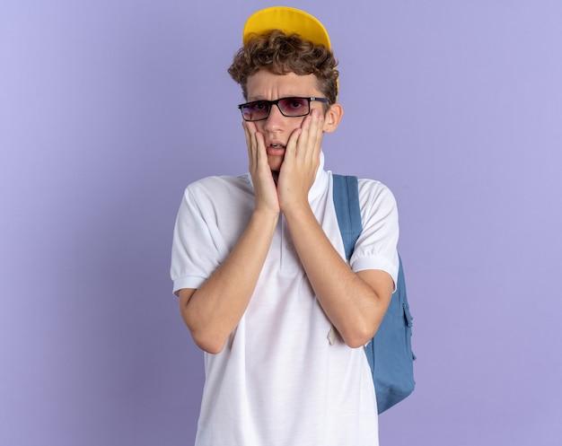 Aluno de camisa pólo branca e boné amarelo usando óculos e mochila olhando para a câmera preocupado em pé sobre um fundo azul