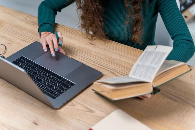 Aluno de close-up trabalhando com laptop e dicionário