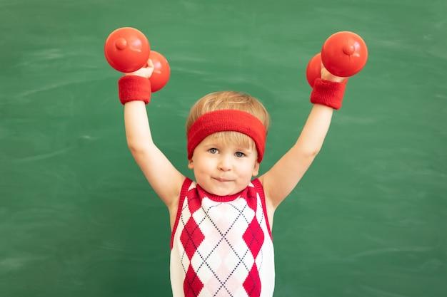 Aluno de criança engraçada em classe contra a lousa verde. educação física.