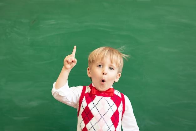 Aluno de criança surpreso apontando o dedo contra a lousa verde.