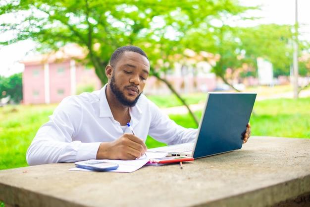 Aluno de etnia alegre usando laptop no campus.