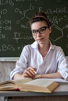 Aluno de jaleco branco e óculos segura um frasco nas mãos e realiza um experimento, universidade de conceito de educação