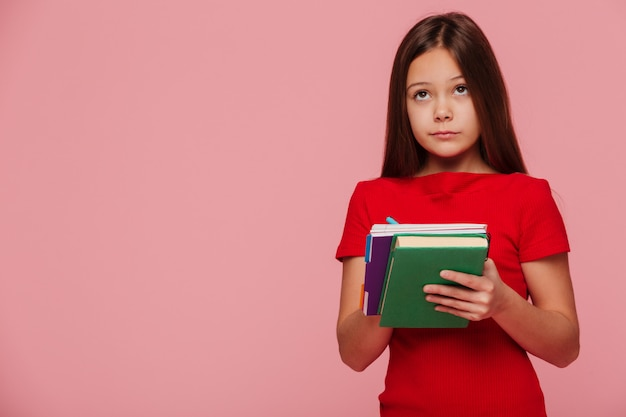 Aluno de menina pensativa olhando para o espaço da cópia e segurando livros