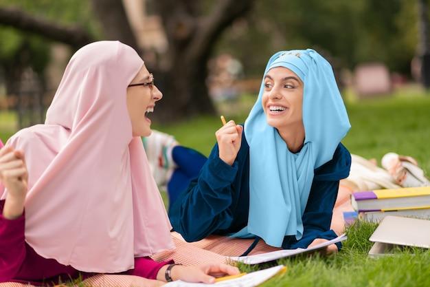 Aluno de óculos. linda estudante muçulmana inteligente usando óculos e estudando ao ar livre com um amigo