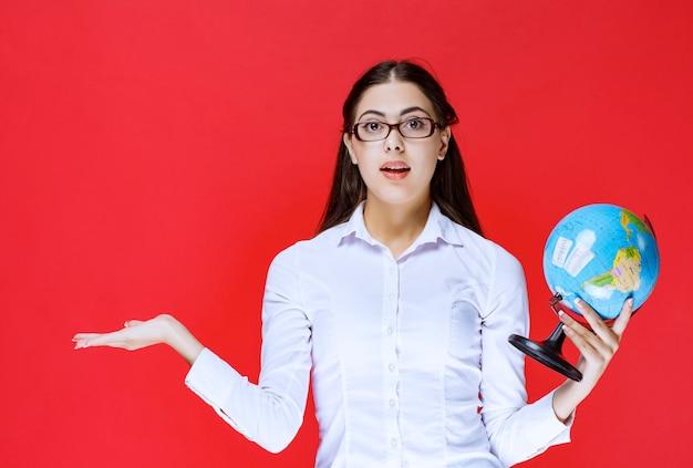 Aluno de óculos segurando e apresentando um globo do mundo.