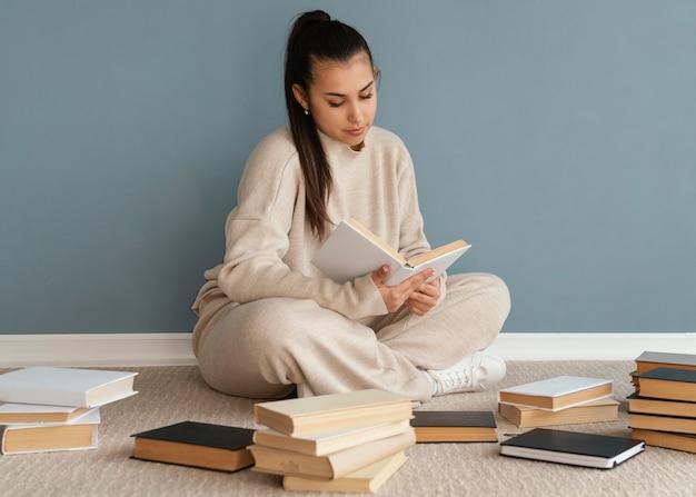 Aluno de tiro completo com livros no chão