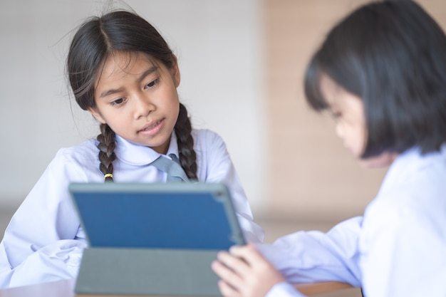 Aluno de volta às aulas estudam juntos usando o tablet digital e escrevem no caderno da escola