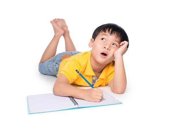 Aluno deitado no chão, olhando para cima e escrevendo no caderno.