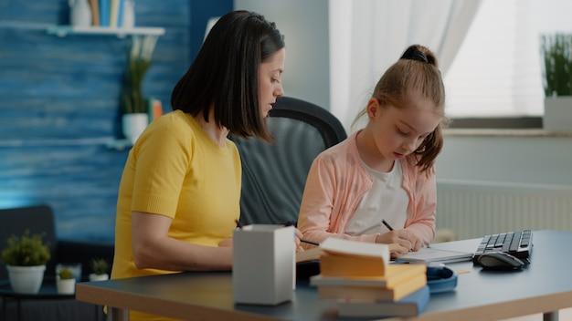 Aluno e mãe fazendo lição de casa junto com livros