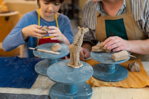 Aluno e seu professor de arte esculpindo uma pequena girafa de argila