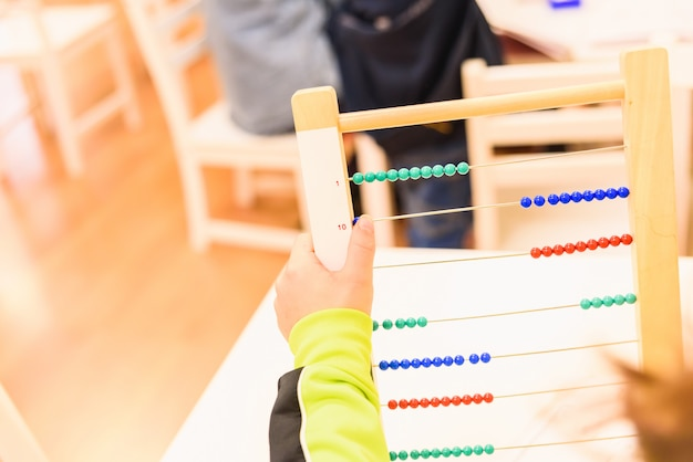 Aluno elementar usando um ábaco para aprender a fazer operações matemáticas