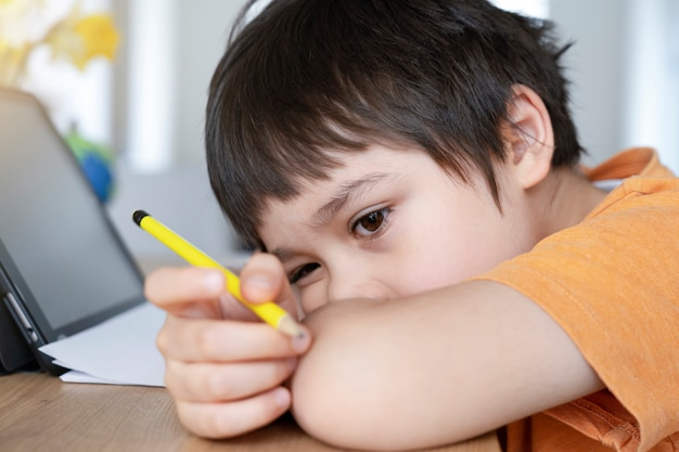 Aluno em auto-isolamento usando o tablet para sua lição de casa, rosto triste criança entediada deitado de cabeça para baixo olhando profundamente no pensamento,
