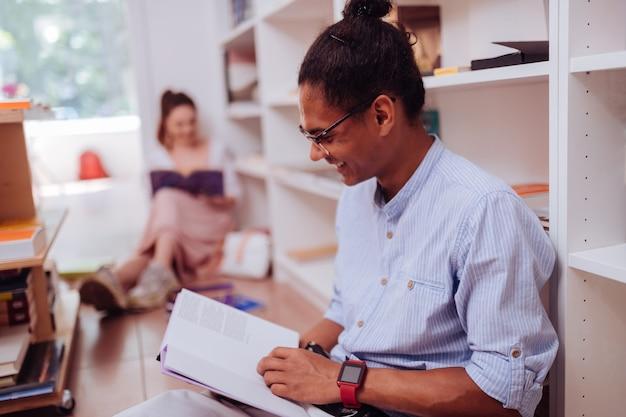 Aluno emocional. aluno gentil de pele escura mantendo um sorriso no rosto enquanto lê o livro