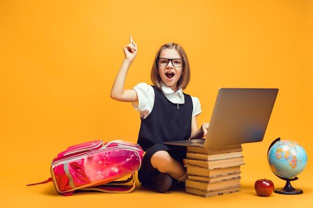 Aluno emocional sentado atrás de uma pilha de livros com o laptop levantando a mão com o dedo indicador educação infantil