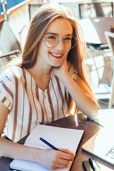 Aluno encantador com cabelo ruivo e sardas fazendo algumas anotações enquanto usa óculos e usa laptop em uma lanchonete