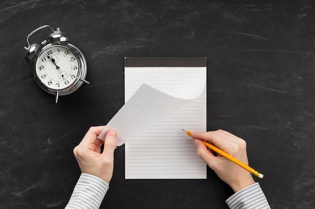 Aluno escrevendo em um bloco de notas vazio