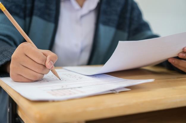 Aluno escrevendo na folha de respostas em papel