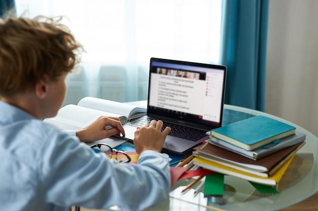Aluno está digitando relatório no laptop, fazendo lição de casa