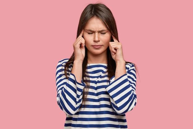 Aluno estressado e sobrecarregado de trabalho mantém os dedos nas têmporas, tem uma expressão desagradável, fecha os olhos