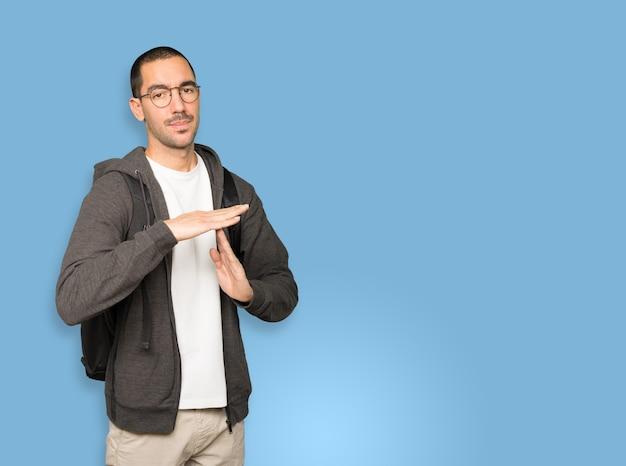 Aluno estressado fazendo um gesto de pausa com as mãos