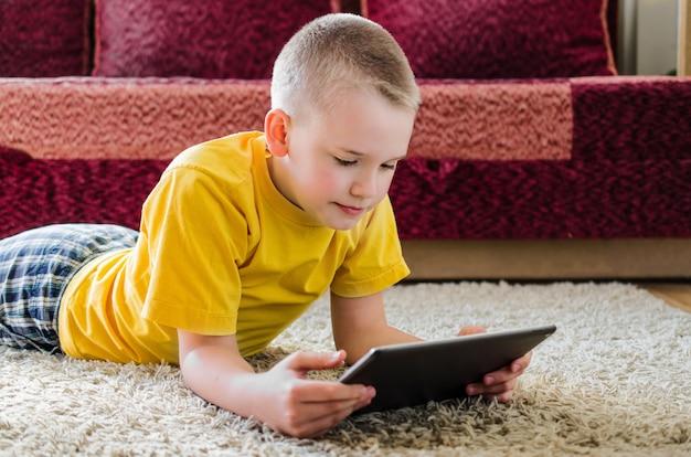 Aluno estudando em casa com tablet digital na mão e fazendo lição de casa da escola