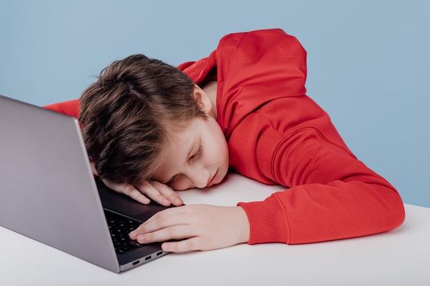 Aluno exausto cochilando na mesa perto do laptop no estúdio sobre fundo azul