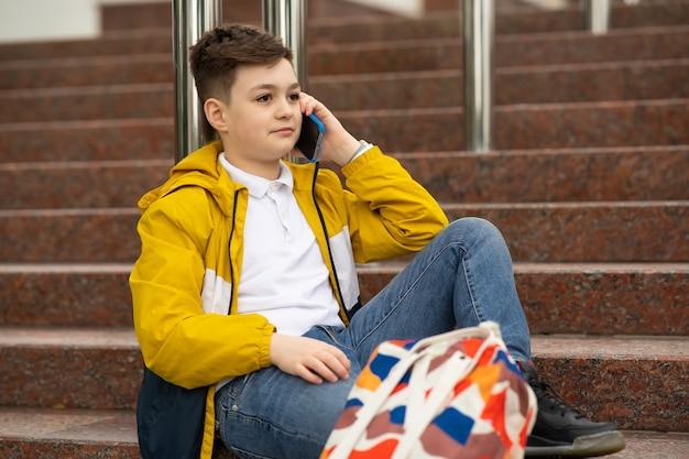 Aluno falando ao telefone, sentado na escada.