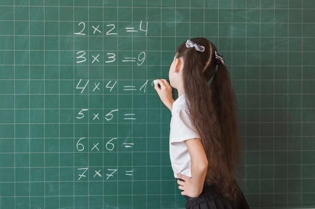 Aluno fazendo exercícios de matemática na lousa Foto Premium