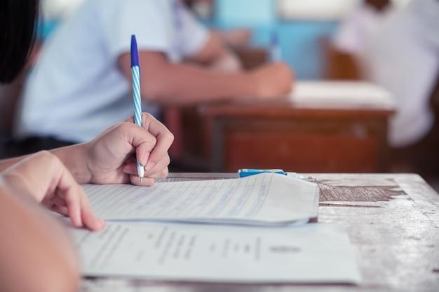 Aluno fazendo teste ou exame na sala de aula da escola com estresse