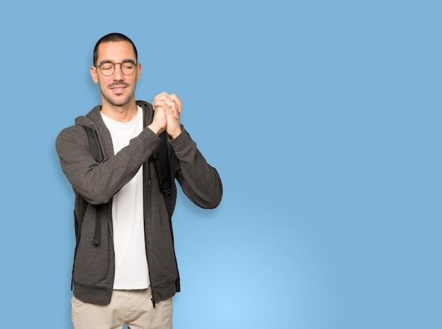 Aluno fazendo um gesto de trabalho em equipe com as mãos