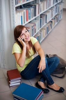 Aluno feliz ao telefone na biblioteca
