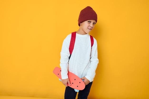 Aluno feliz com mochila vermelha skate vermelho fundo de cor amarela