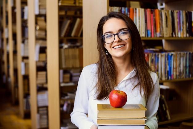 Aluno feliz com muitos livros e uma maçã na biblioteca