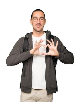 Aluno feliz fazendo um gesto de amor com as mãos