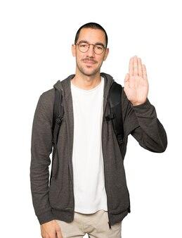 Aluno feliz fazendo um gesto de parar com a palma da mão