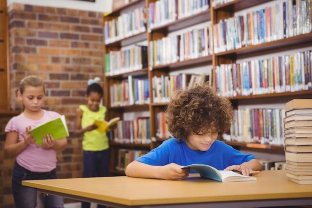 Aluno feliz lendo um livro da biblioteca na escola primária