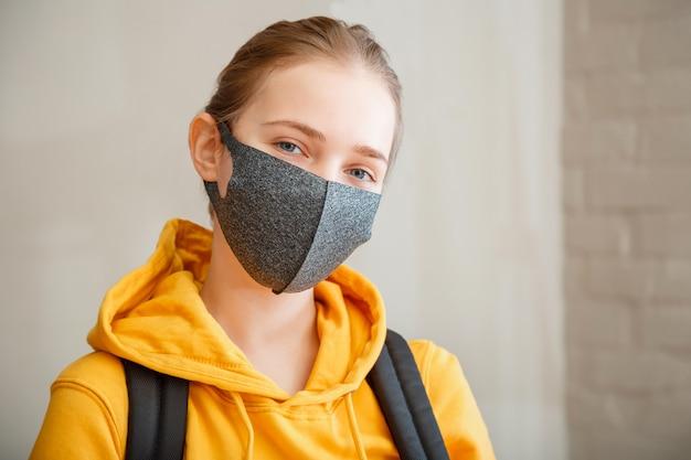 Aluno feliz na parede de tijolos com espaço de cópia. jovem e bela mulher sorri sinceramente, usando o retrato de máscara protetora com mochila. adolescente loira caucasiana adolescente viajante na máscara.